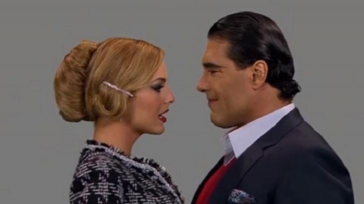 Cena de Amores Verdadeiros com Jose Angelo vestido de terno e gravata sorrindo de frente para outra mulher, elegante