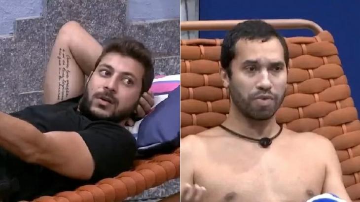 Caio está deitado em poltrona com as mãos atrás da cabeça enquanto Gilberto está sentado em cadeira gesticulando
