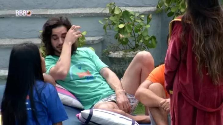 Fiuk está chorando com a mão no rosto ao lado de Pocah e Juliette na área externa do BBB21