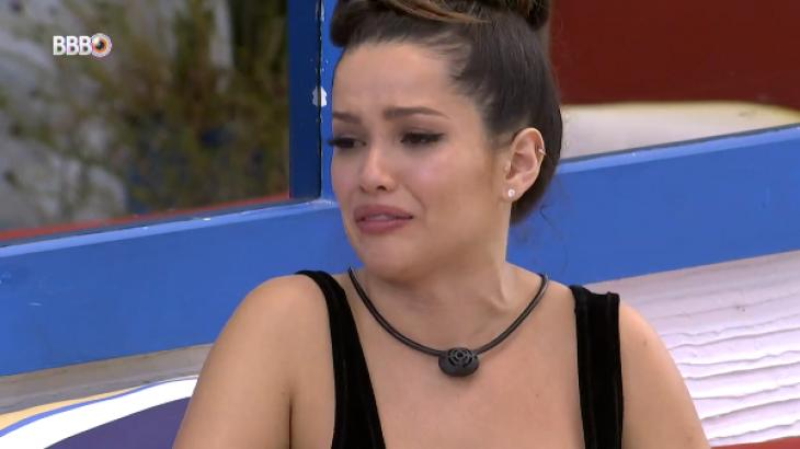 Juliette está chorando vestida com uma camiseta preta e de coque na área externa do BBB21