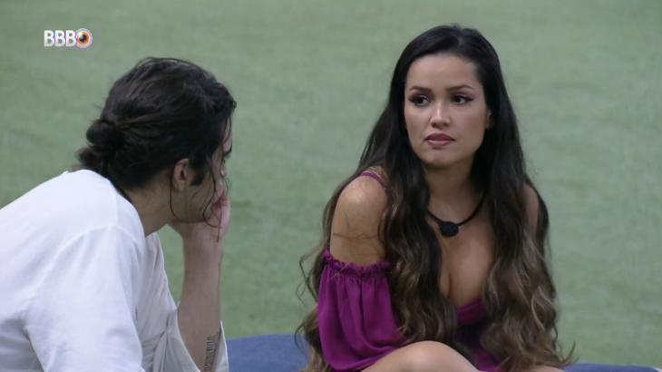 Juliette está de frente para Fiuk na área externa do BBB21 conversando sentada com o brother