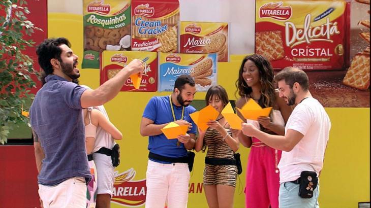 Rodolffo, Gilberto, Thaís, Camilla de Lucas e Caio segurando um envelope laranja e lendo o recado dos fãs do BBB21 na área externa da casa21