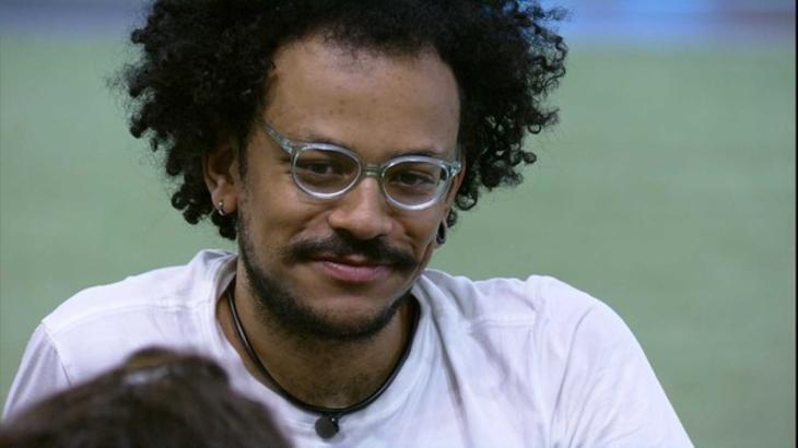 João Luiz sentado no gramado do BBB21