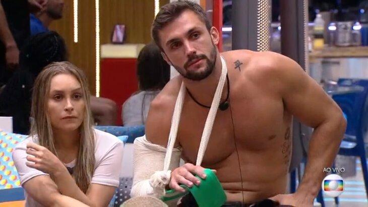 Arthur com braço enfaixado e com tala, durante programa ao vivo, ao lado de Carla Diaz
