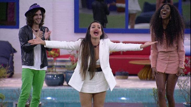 Fiuk batendo palma, Juliette de braços abertos e Camilla de Lucas gritando estão comemorando na área externa do BBB21