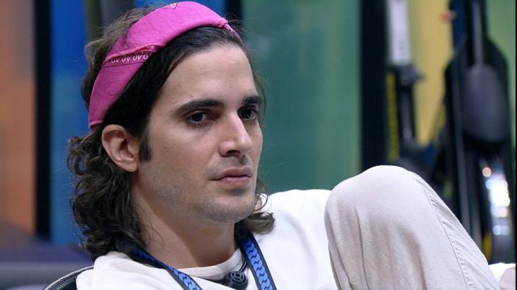 Fiuk de bandana rosa e roupa branca sentado na academia do BBB21 analisando jogo
