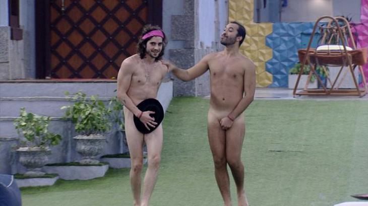 Fiuk e Gilberto estão pelados escondendo as partes íntimas com a mão e um chapéu caminhando até a piscina do BBB21