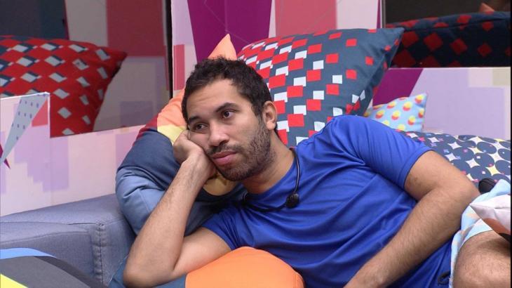 Gilberto está deitado no sofá da sala do BBB21 com a mão do rosto