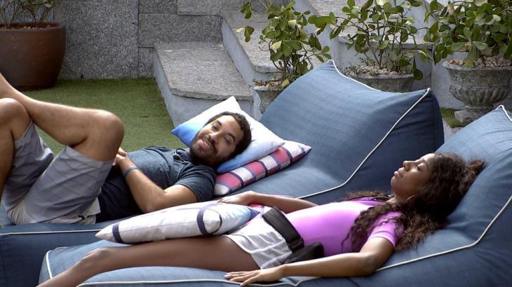 Gilberto e Camilla de Lucas estão deitados em poltrona na área externa do BBB21