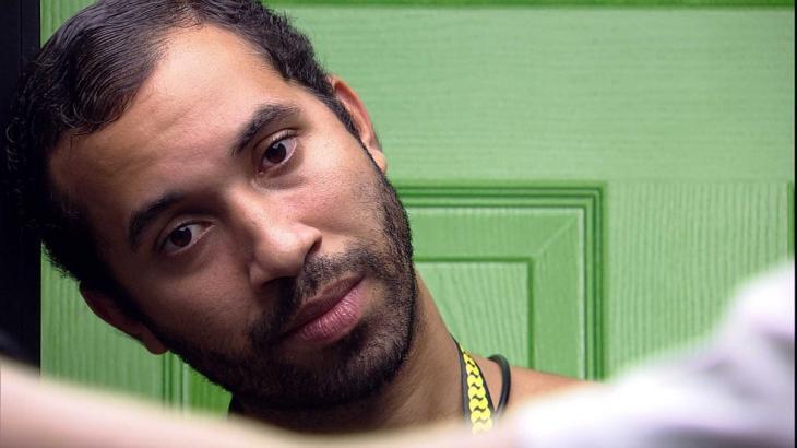 Gilberto com a cabeça encostada na parede com semblante pensativo