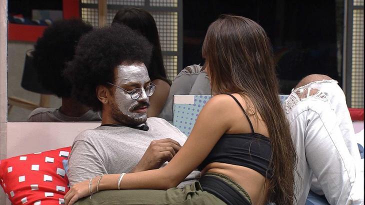 Na sala, João Luiz está com máscara no rosto e conversa com Thaís