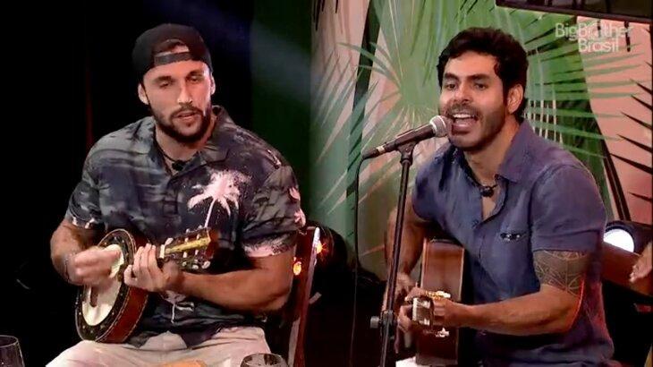 Rodolffo cantando e tocando violão, enquanto Arthur também toca instrumento