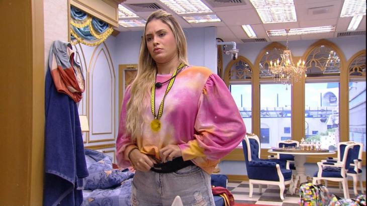Sarah se arruma em frente ao espelho do quarto do líder
