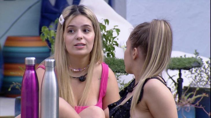 Na área externa, Viih Tube conversa com Carla Diaz; as duas estão sentadas no gramado