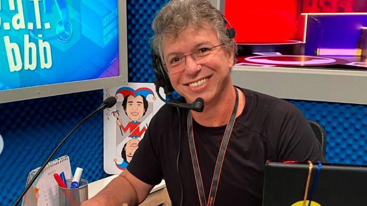"""Boninho sorrindo no cenário do """"CAT BBB"""" com fone e microfone"""