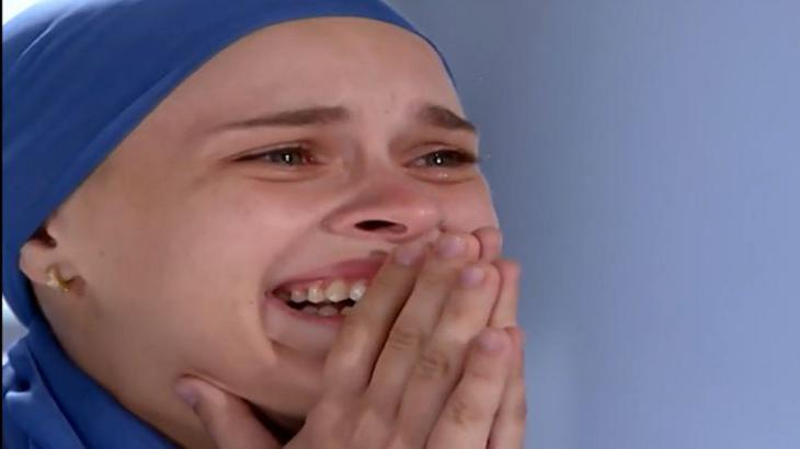 Camila com as mãos na boca chorando de felicidade