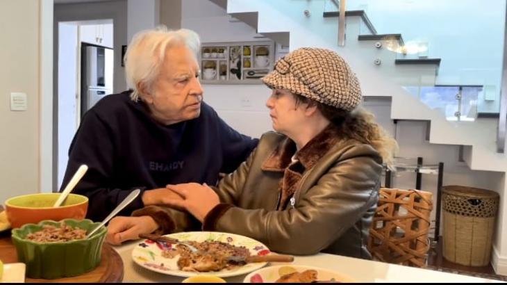 Cid Moreira e a mulher, Fátima Sampaio, sentando em uma mesa olhando um para o outro