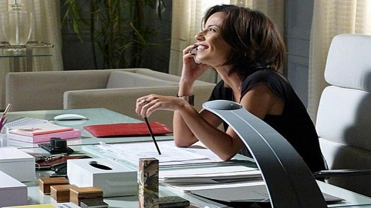 Clara sorrindo enquanto fala ao celular com Vicente