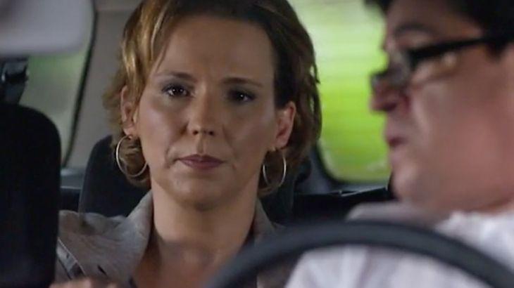 Eva com expressão séria observa a filha de dentro de um táxi