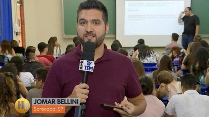 Jomar Bellini em uma sala de aula cheia de estudante e professor, durante link, segurando microfone,