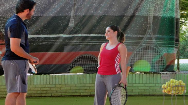 Cena de A Vida da Gente com Lúcio e Ana frente a frente, os dois segurando raquetes de tênis