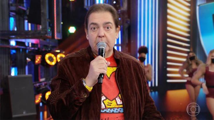 O apresentador Faustão em seu programa da Globo segurando um microfone, de jaqueta marrom e relógio amarelo