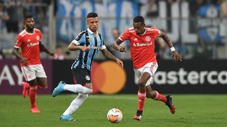 Jogadores de Internacional e Grêmio jogando futebol