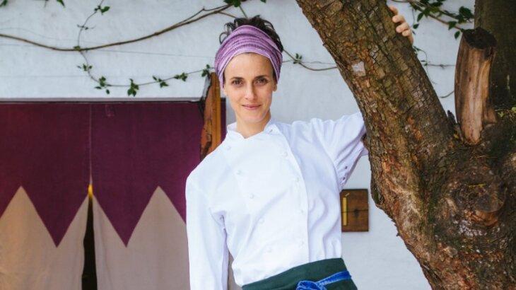 Com uniforme de chef, Helena Rizzo com a mão em uma árvore, posada para foto