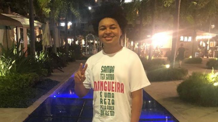 JP Rufino com camisa de samba fazendo sinal de V com os dedos