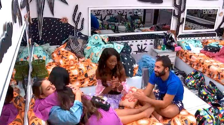 Juliette abraçando Sarah na cama do quarto cordel do BBB21 enquanto Camilla de Lucas e Gilberto batem palma sorrindo