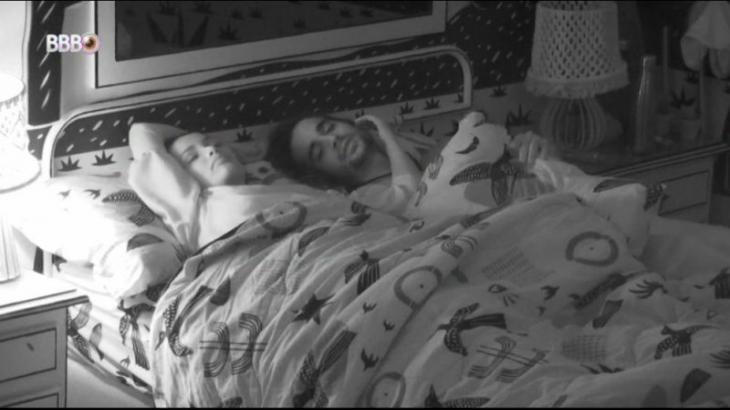 Juliette e Fiuk estão deitados no escuro na cama de casal do quarto cordel do BBB21 enquanto a sister faz carinho no rosto do brother