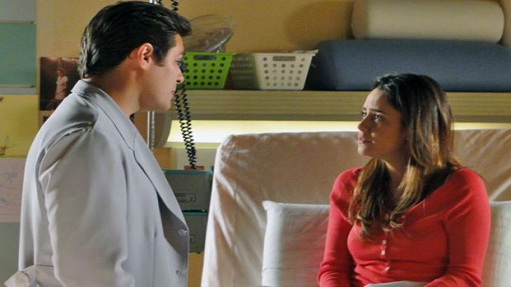 Lúcio em pé na beira da cama de Ana enquanto conversa