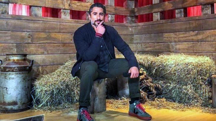 Marcos Mion aparece sentado dentro da fazenda