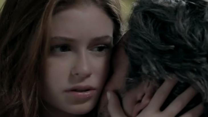 Isis pensativa enquanto José Alfredo beija sua pescoço