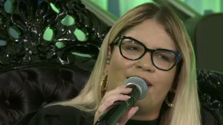 Marília Mendonça cantando de óculos