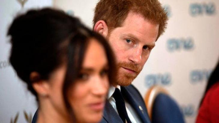Príncipe Harry olhando de lado, no vazio e Meghan Markle à frente desfocada
