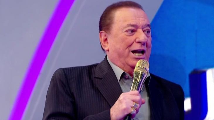 Raul Gil em seu programa no SBT segurando o tradicional microfone dourado - Reprodução/SBT