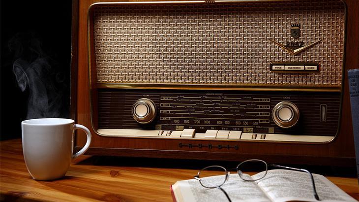Radio antigo em cima da mesa ao lado de uma xícara de café e um óculos localizado em cima de um livro