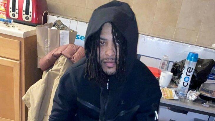 Rapper KTS Dre sentado, com capuz na cabeça