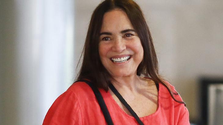 Regina Duarte sorrindo com um vestido vermelho
