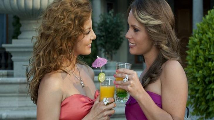 Renata e Roberta brindam enquanto se encaram