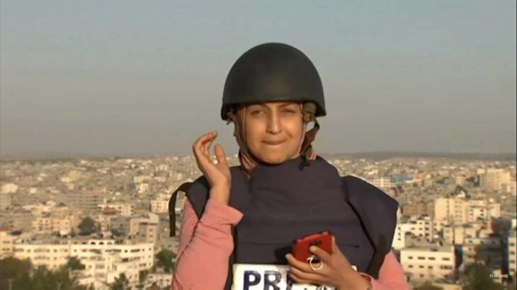 Repórter tensa levando a mão no ouvido, com celular na outra mão