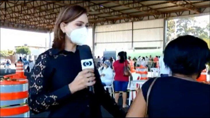 Com microfone na mão, repórter reclama de mulher