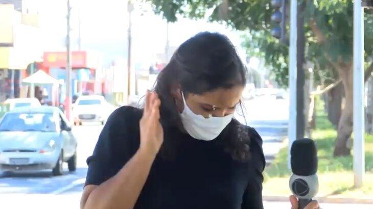 Repórter com a cabeça abaixada logo após ser atingida por fezes de pombo