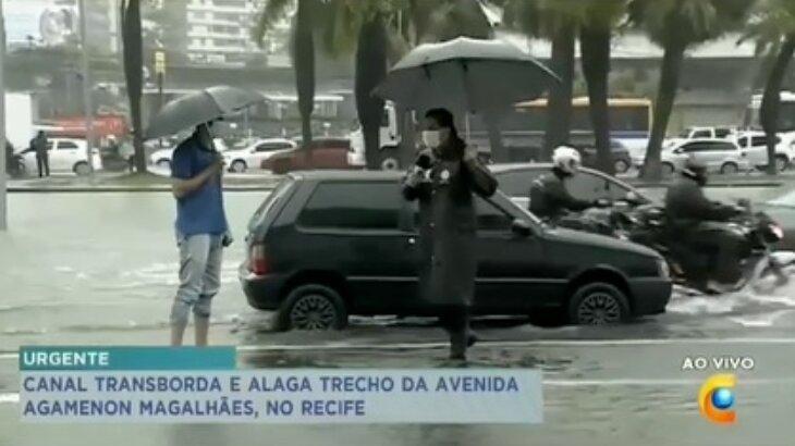 Repórter se encaminha para entrevistas pessoa, durante o alagamento, com guarda-chuva em uma mãe e microfone na outra