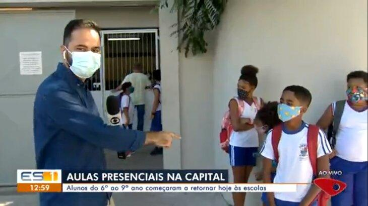 Repórter segura microfone e aponta para menino, que está com máscara e mochila nas costas, pronto para ser entrevistado