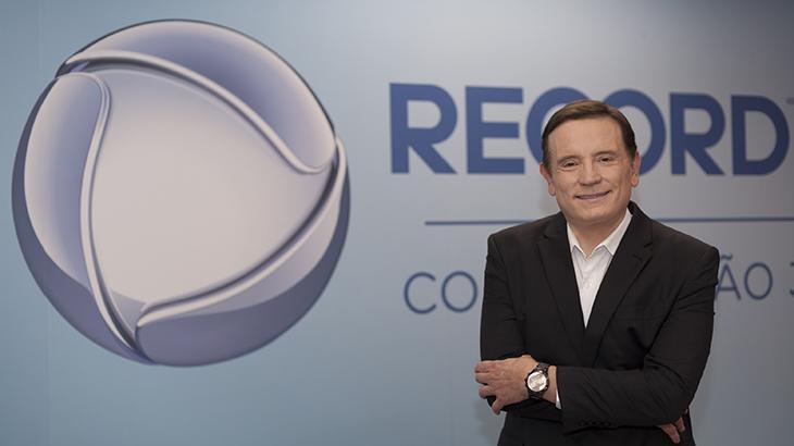 Roberto Cabrini de braços cruzados ao lado do logo da emissora