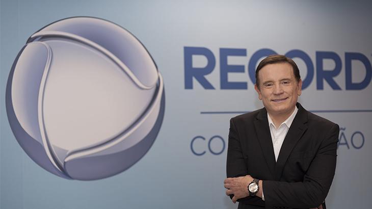 Roberto Cabrini posa sorrindo tendo ao fundo o logotipo da Record