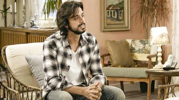 Alejandro sentado na sala da casa da avó de Gabi