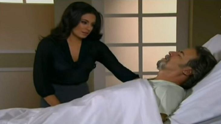 Cena de Coração Indomável com Alessandro deitado na cama do hospital, olhos fechados e coberto e Maricruz de pé, ao lado, olhando para ele